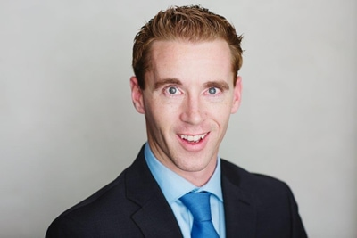 Young male criminal defense attorney wearing a blue suit and tie posing for a headshot photo