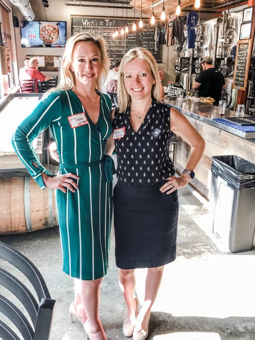Two blonde female attorneys in business casual attire next to one another taking a picture at a brewery