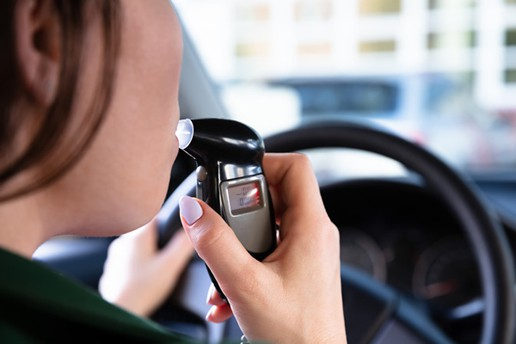 Woman in her vehicle blowing on a ignition interlock device to test her blood alcohol level.