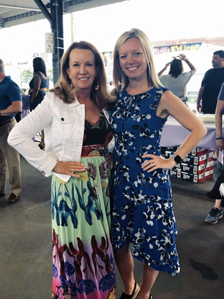 Brunette woman in a bright multi colored dress on the left alongside a blonde woman in a blue dress with white flowers.