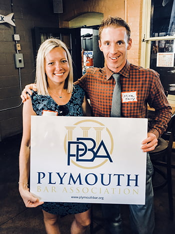 Two young blonde male and female attorneys taking a picture while holding a sign that says Plymouth Bar Association