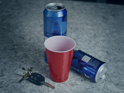 Car keys next to empty beer cans and a red solo cup symbolizing a possible DUI
