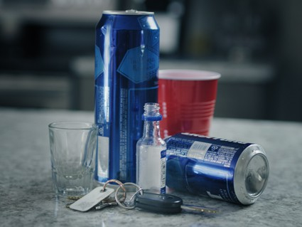 Car keys next to empty booze bottles and a red solo cup symbolizing a possible MIP charge at a party with underage drinking