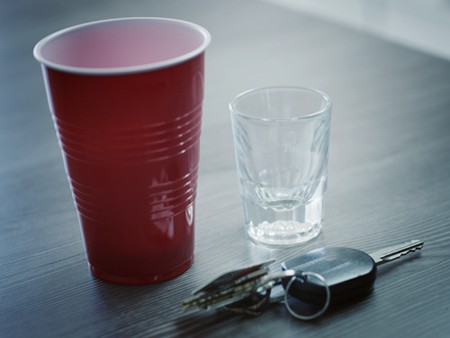 Car keys next to empty shot glass and red solo cup symbolizing a possible DUI