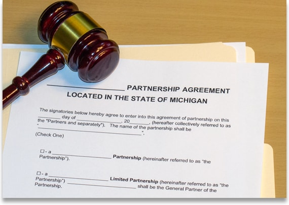 Business attorney document on a desk titled 'Partnership Agreement Located in the State of Michigan.' The document is next to a gavel and yellow folder.