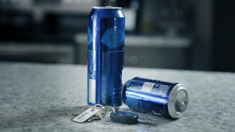 Two open beer cans next to a set of keys representing open container law