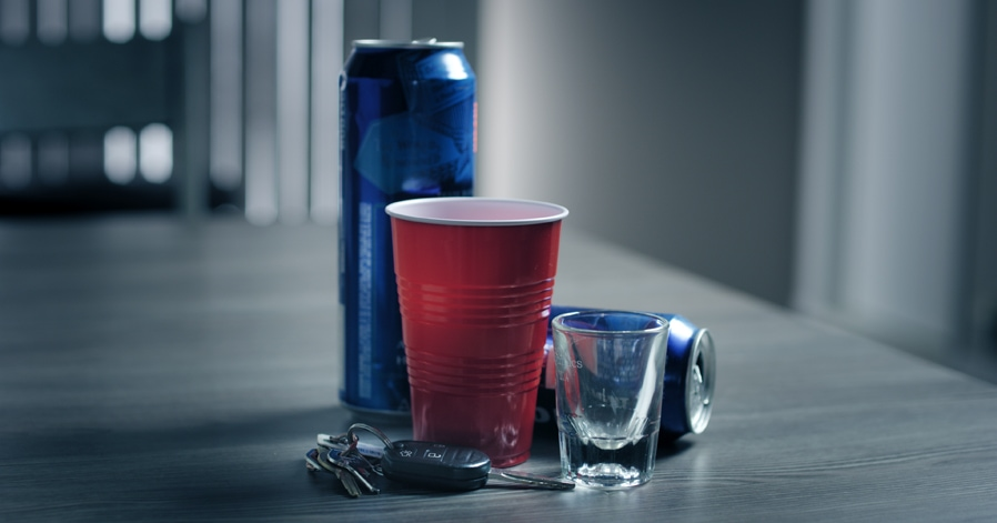Car Keys on a table next to several beer cans and a red cup, symbolizing a DUI