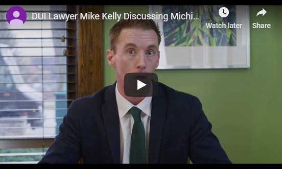 Young DUI lawyer Mike Kelly sitting down at a desk discussing the topic of drunk driving charges in Michigan