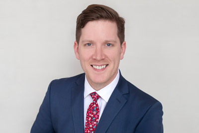 Headshot of a young attorney with a bright red festive tie.