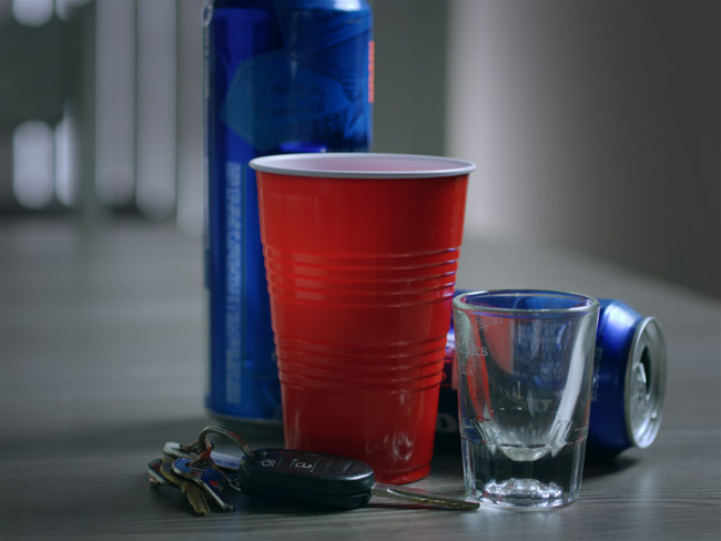 Image of someone's car keys next to open alcohol containers symbolizing a potential OWI